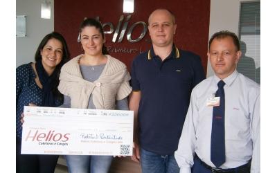 Foto com o Diretor da empresa, a associada de Palmitos/SC senhora Cristiane Manica e demais funcionários da empresa. Ao fundo a logo da empresa em fundo vermelho e letras em alumíno.