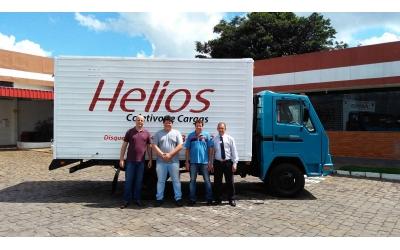Foto de um veículo 3x4 com carroceria baú na cor branca e logo da Helios em vermelho, com cabina azul. À frente funcionários e associados da empresa da cidade de Santo Antonio do Sudoeste/PR.