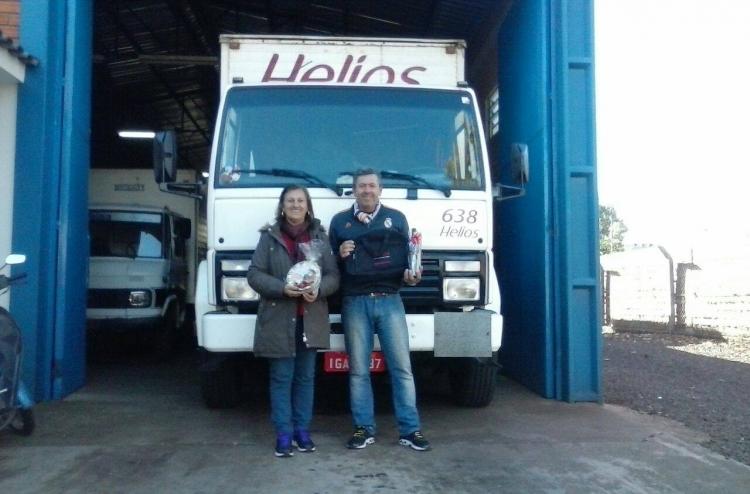 Um homem e uma mulher em frente a uma garagem segurando um premio.
